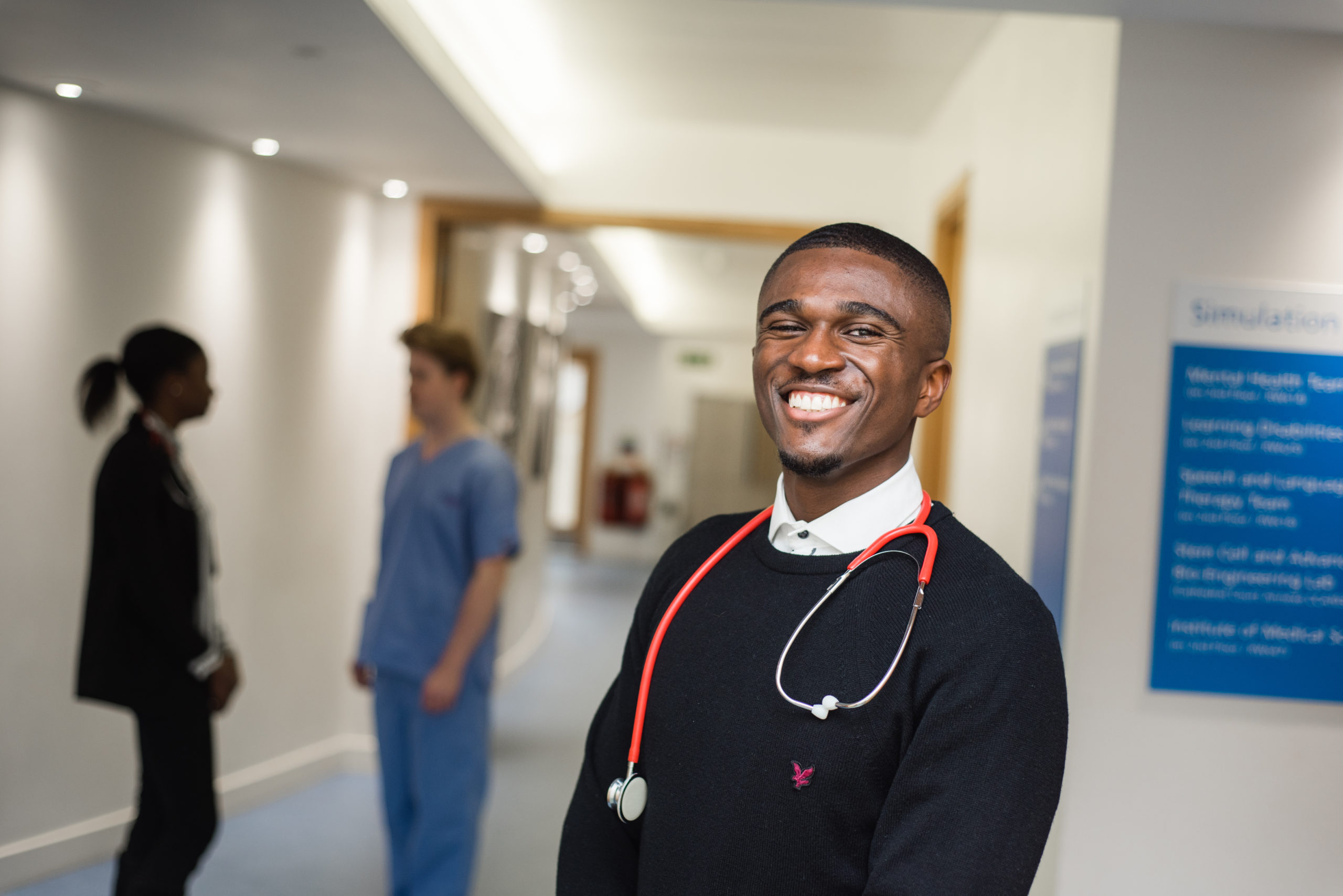 Focus on smiling male medical student with stethoscope around neck