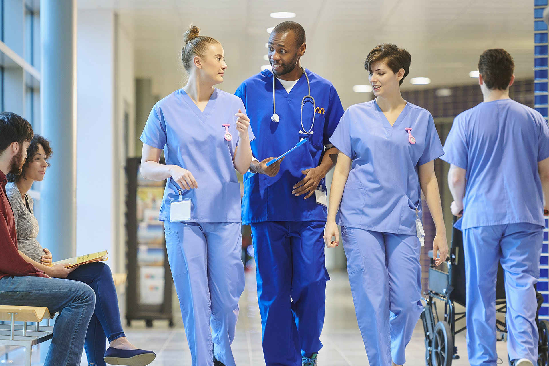 Health staff walk along a hospital corridor