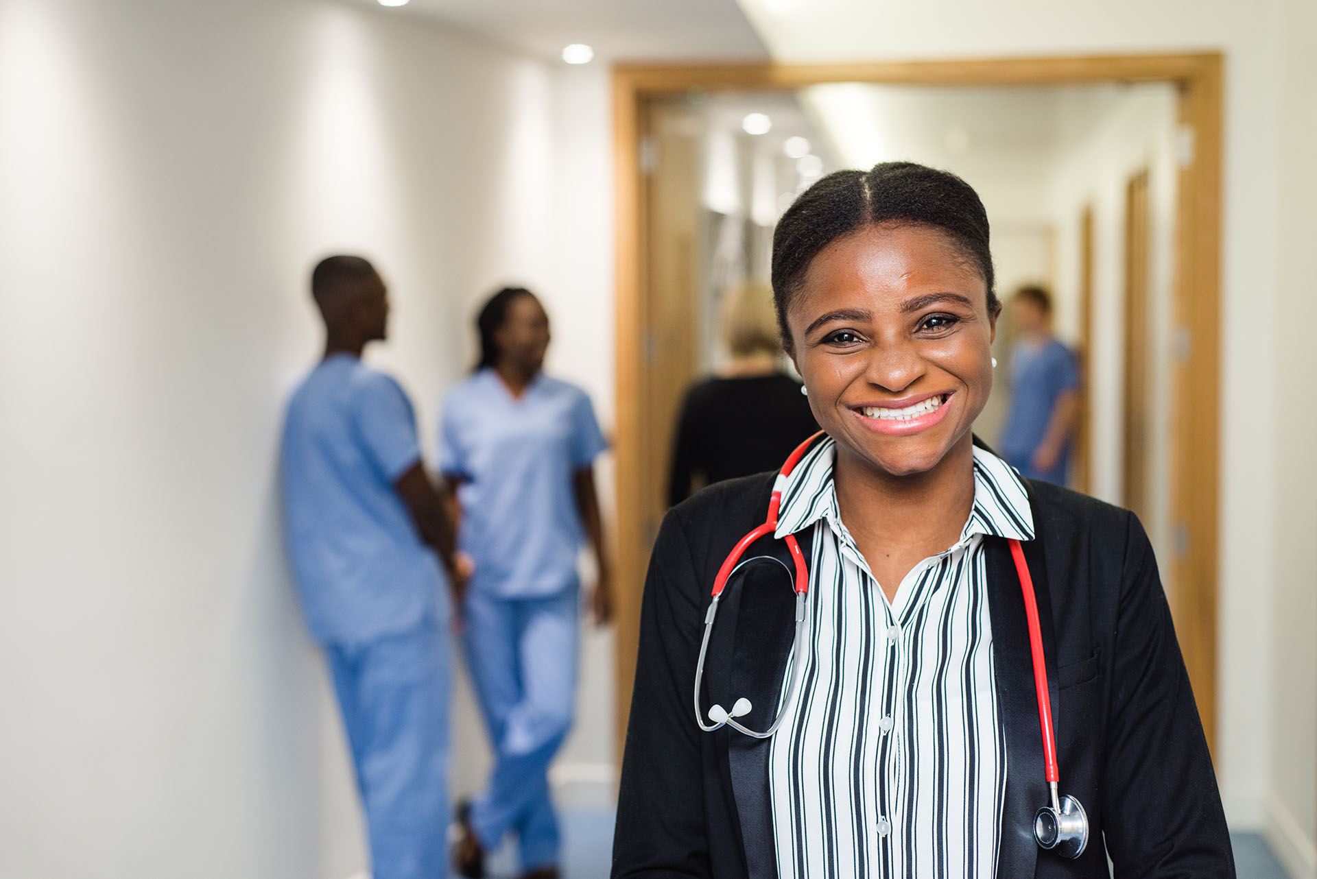 Health professional smiling with stethoscope, other health professionals in background