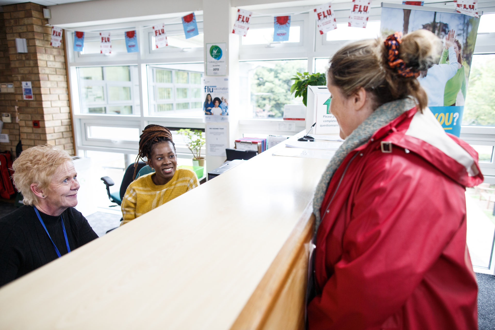 Female in red jacket at reception desk