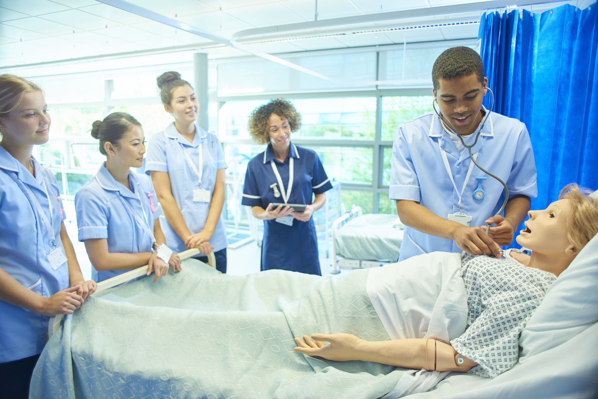 Students in simulation suite with one of them listening to the breathing of medical mannequin