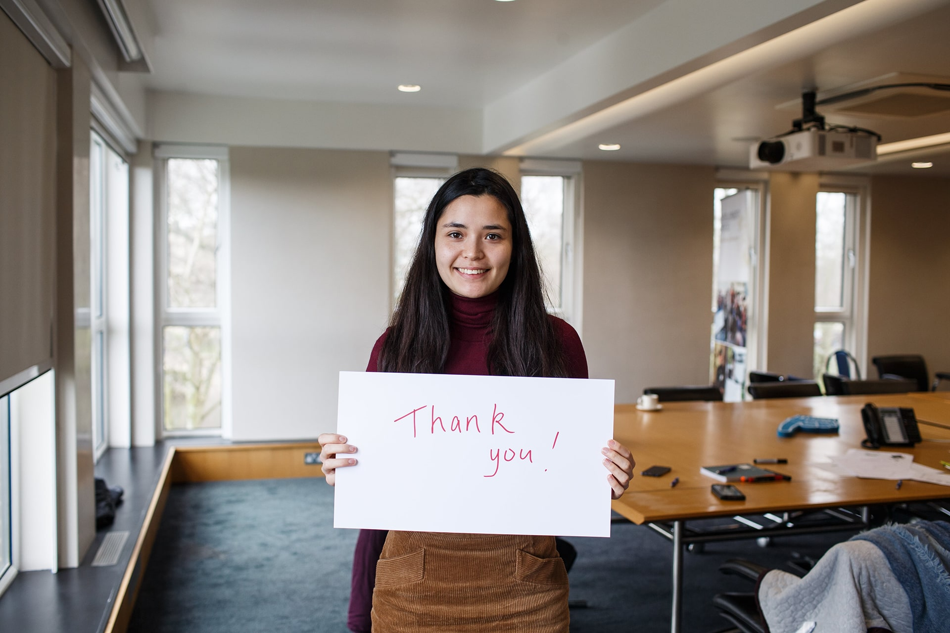 Photo of a person holding a card with the words Thank You written on it